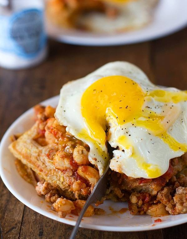These chili and cornbread waffle stacks start with a plate of delicious cornbread waffles, topped with chili and a fried egg. YUM. | pinchofyum.com