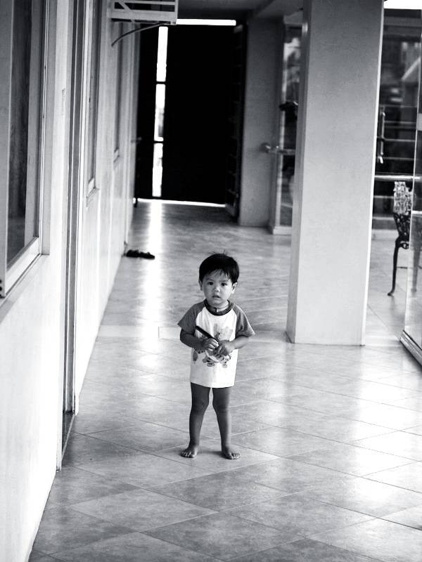 Boy standing in a hallway.