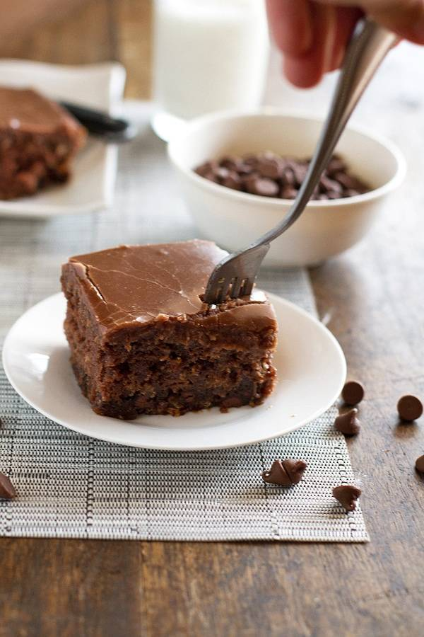 One piece of chocolate oatmeal cake on a white plate with a fork.