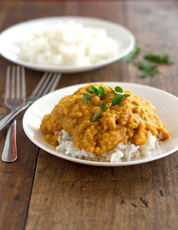 Red lentil dhal on a white plate with two forks.
