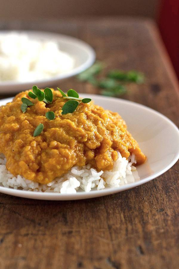 Red lentil dhal with rice on a white plate.