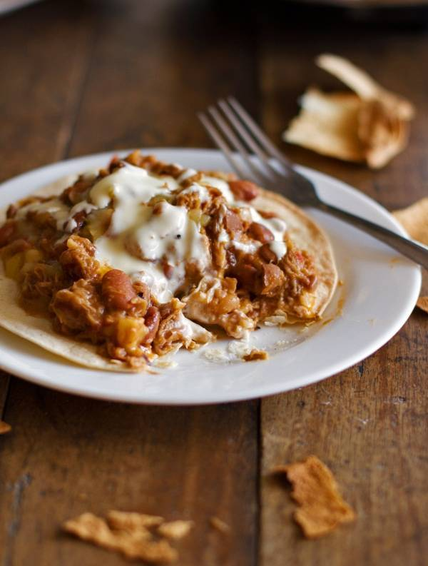 These crockpot chalupas are so easy to make and so addicting! Shredded Mexican flavored pork and pinto beans over a baked crispy tortilla. Yum! | pinchofyum.com