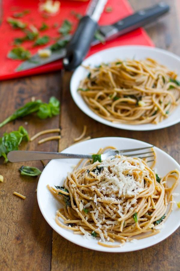 Garlic butter spaghetti with herbs on two white plates.