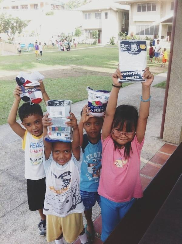 Young kids holding clothing.