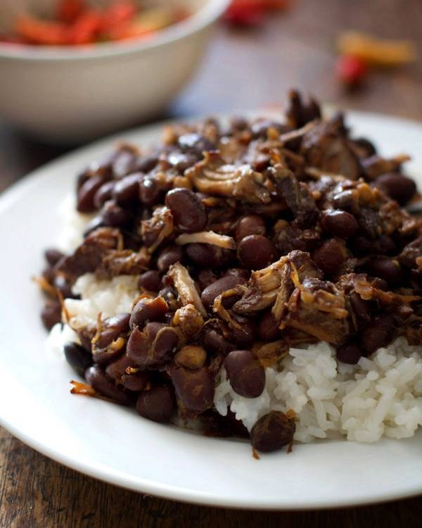Pork adobo with black beans and rice on a white plate.