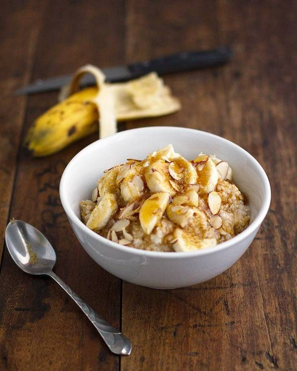 Steel cut oats with bananas in a white bowl with a spoon.