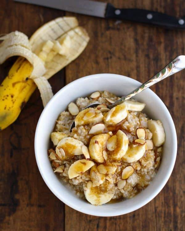 Steel cut oats with bananas in a white bowl.