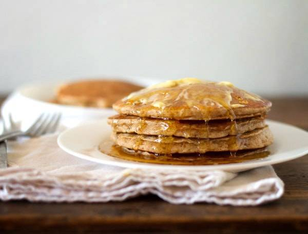 Whole wheat pancakes stacked on a plate with syrup.