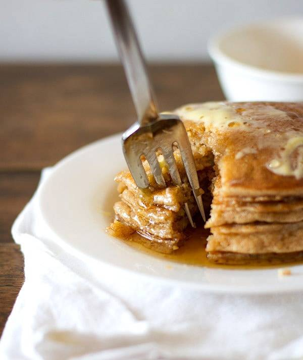 Whole wheat pancakes stacked on a plate with a fork removing a bite.