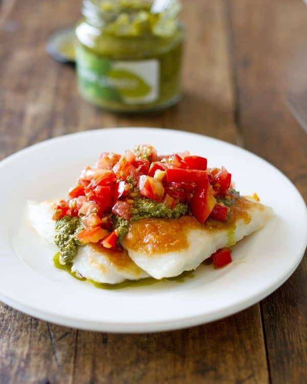 This simple Parmesan pesto tilapia is broiled to a cheesy golden perfection and topped with pesto and fresh chopped tomatoes. Just 5 ingredients. | pinchofyum.com