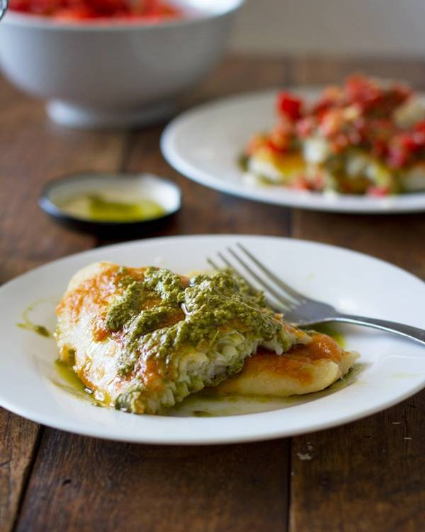 Parmesan pesto tilapia on a plate with a fork.