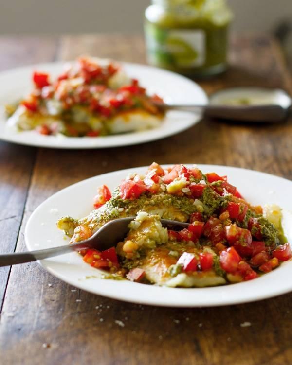 Parmesan pesto tilapia on two white plates.