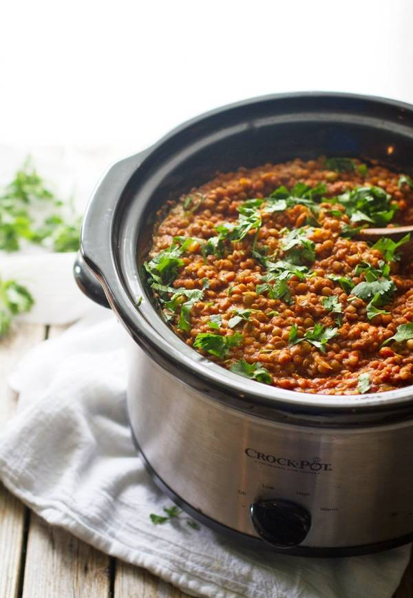 Red lentil curry in a crockpot with herbs.