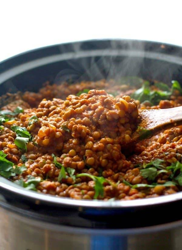Red lentil curry in a crockpot on a wooden spoon.