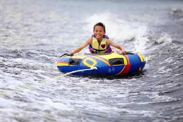 Boy tubing on the lake.