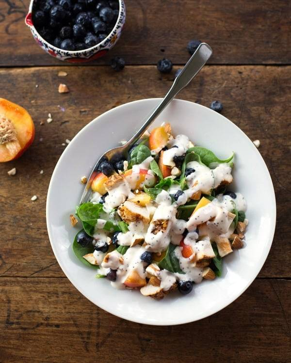 Chicken and nectarine poppy seed salad in a white bowl.