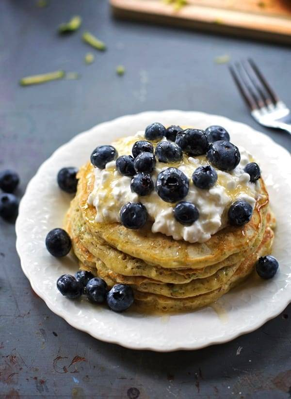 Stack of zucchini pancakes with blueberries.