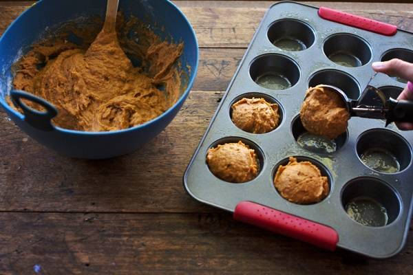 Muffin mix in a blue bowl and being scooped into a muffin tin.