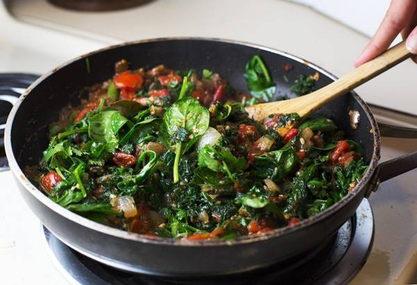 Palak paneer in a skillet with a wooden spoon.