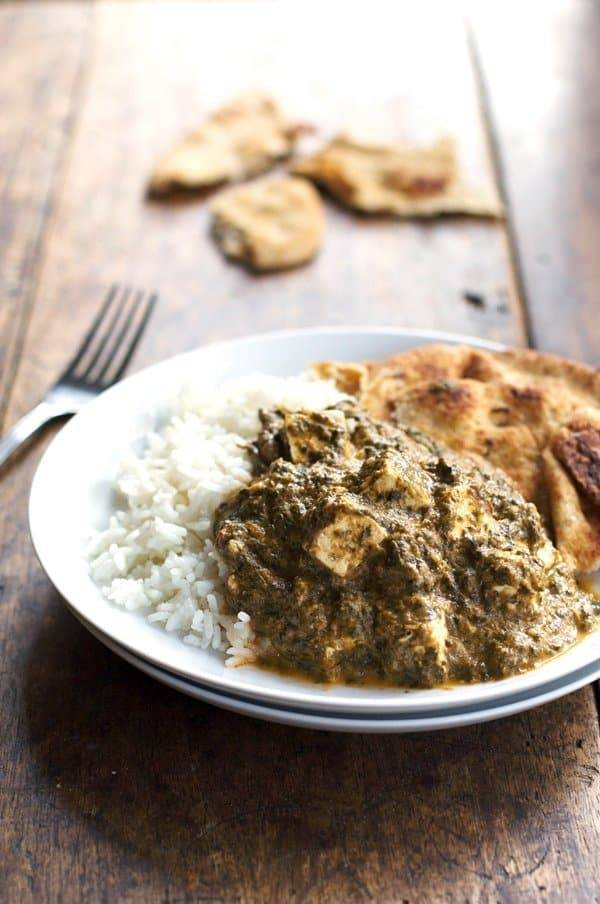 Palak paneer with rice on a plate.
