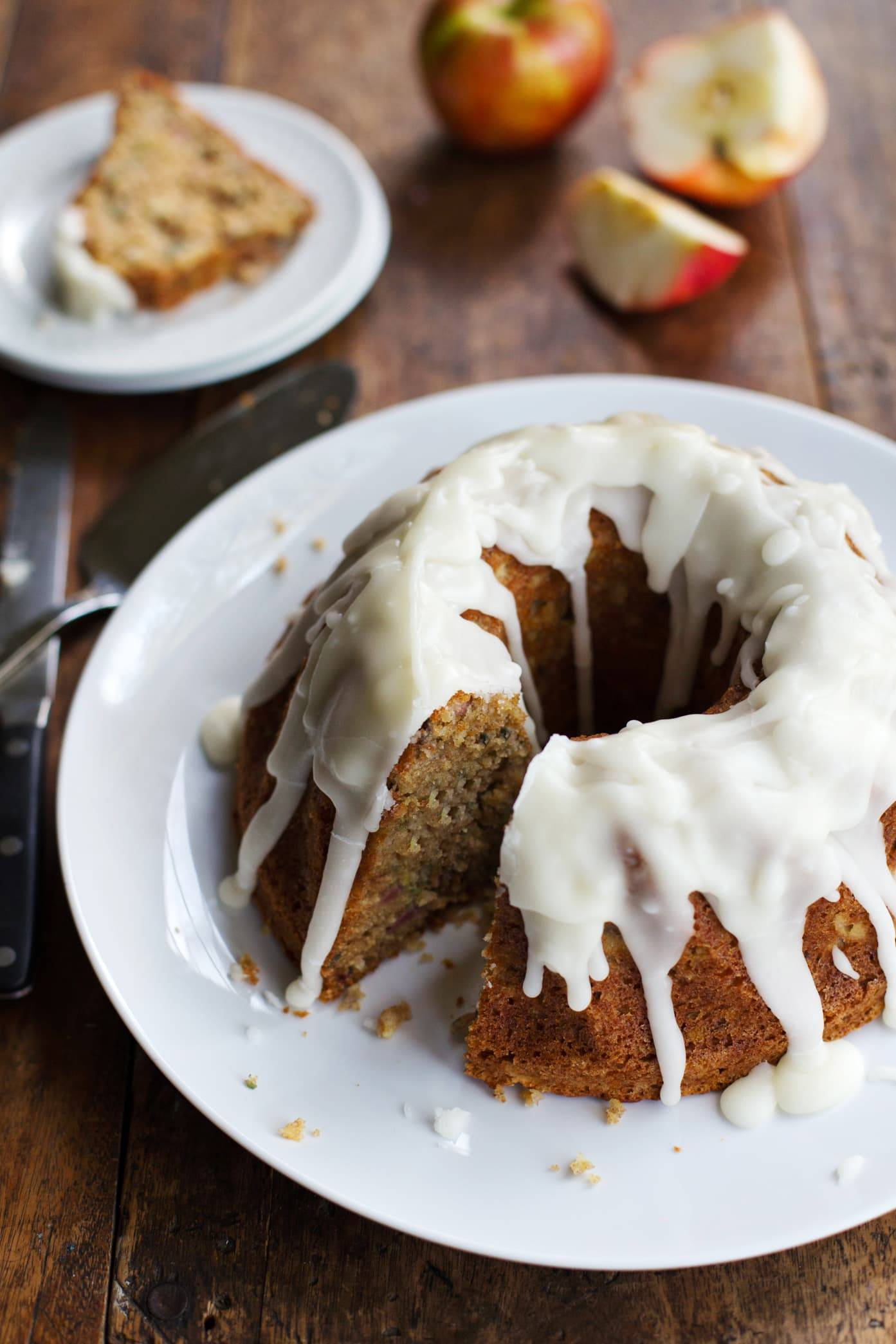 Honey apple bundt cake with glaze on a plate.