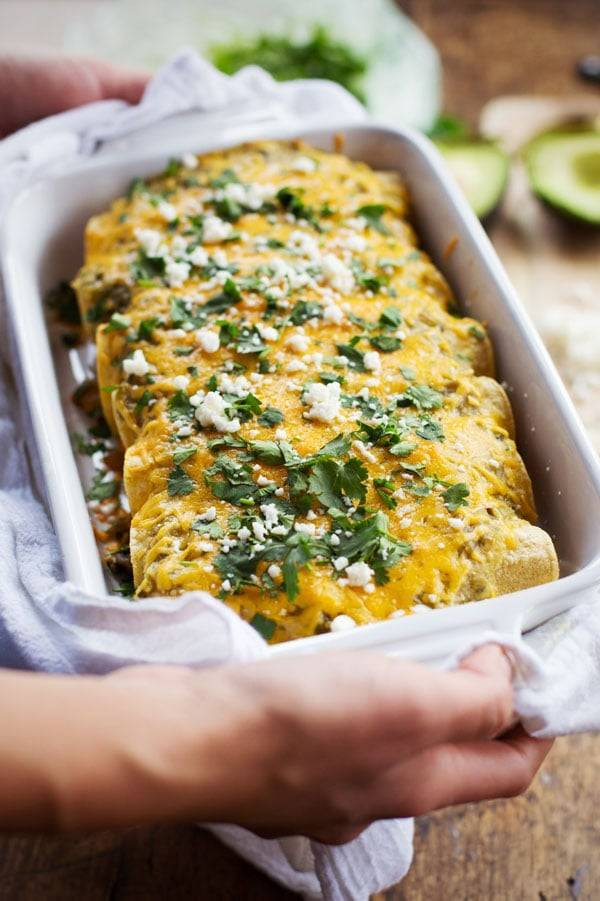Butternut Squash and Mushroom Enchiladas with Tomatillo Sauce in a white dish.