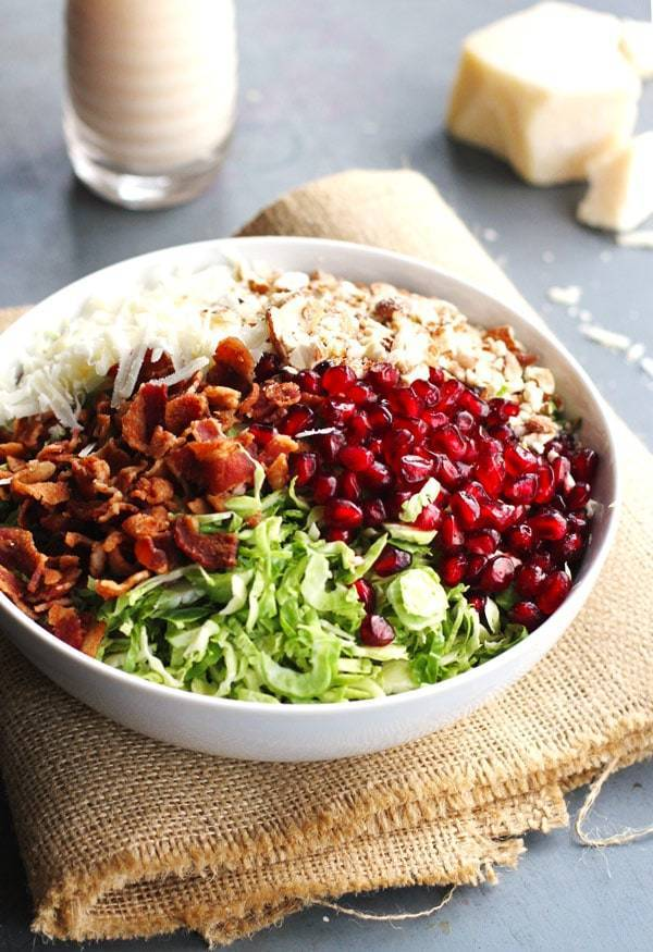 Brussels sprout salad has pomegranates, almonds, crumbled bacon, and homemade creamy salad dressing in a white bowl.