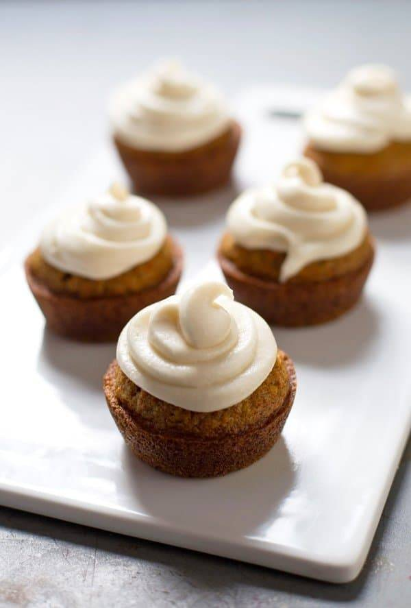 Carrot cake cupcakes with frosting on a white surface.