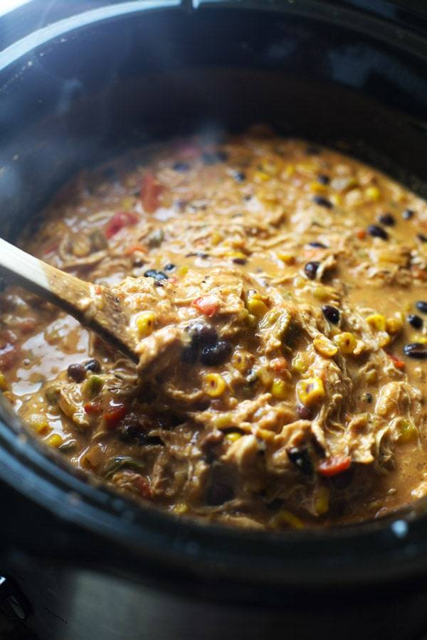 Queso Crockpot Chicken Chili in a crockpot with a wooden spoon.