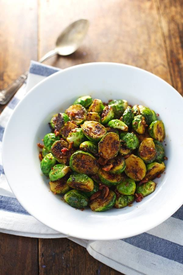Caramelized brussels sprouts in a blue bowl with a spoon.