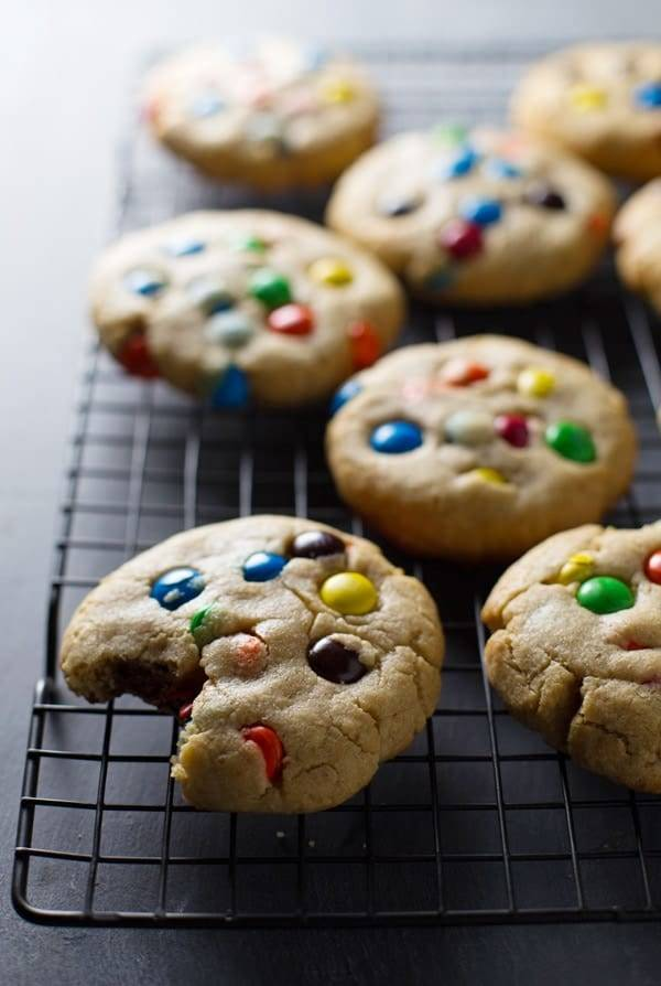 Big soft M&M cookies on a drying rack.