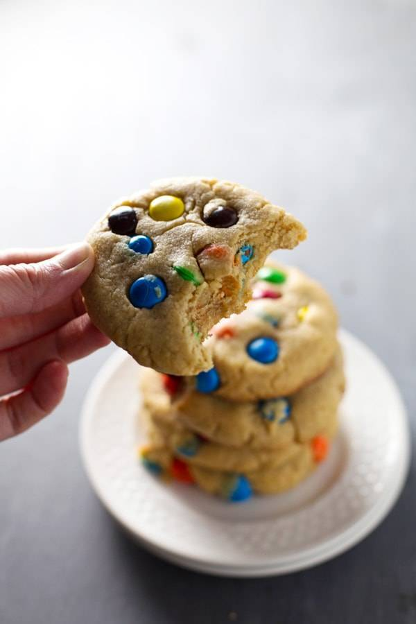 Big soft M&M cookies on a stack of white plates.
