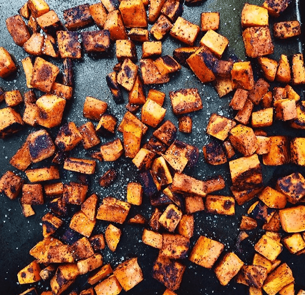 Sweet potatoes roasting on a black surface.