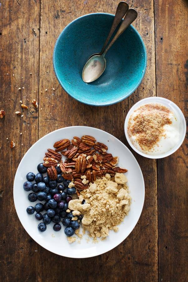 Plate with blueberries, pecans, and yogurt next to a blue bowl with spoons.