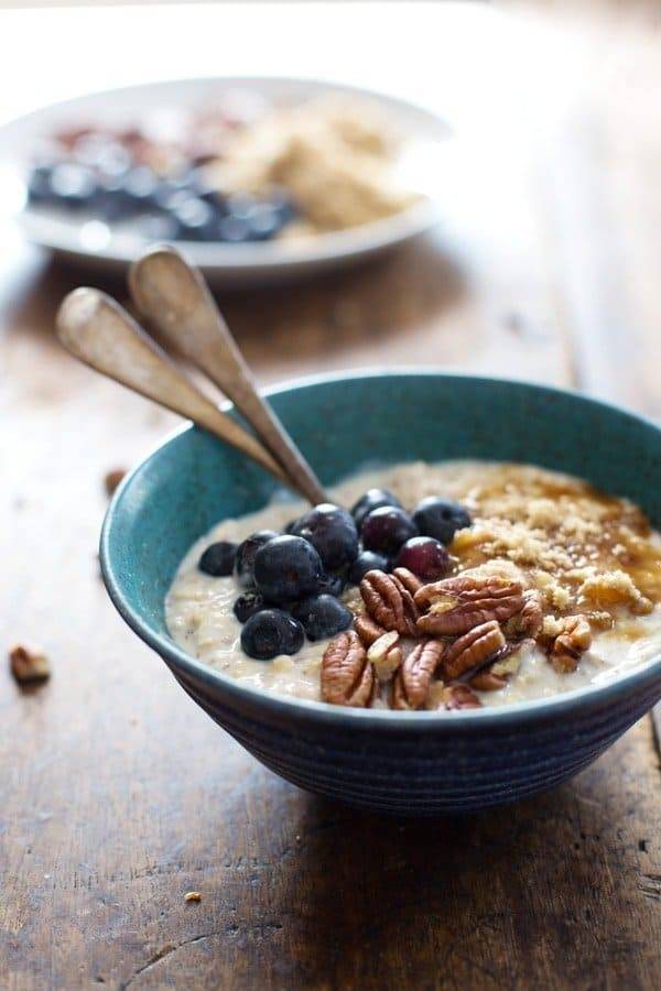 Overnight oats with flax, blueberry, and vanilla yogurt in a blue bowl with spoons.