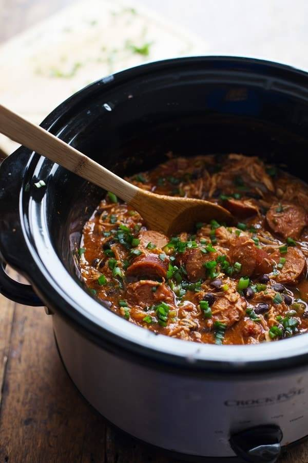 Creole Chicken and Sausage in a crockpot with a wooden spoon.