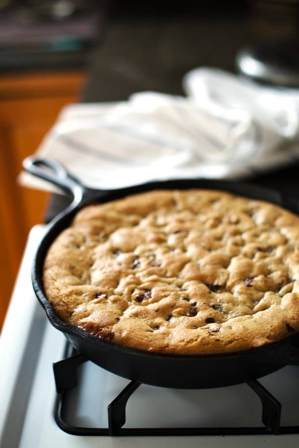 Deep Dish Chocolate Chip Cookie in a skillet on the oven.