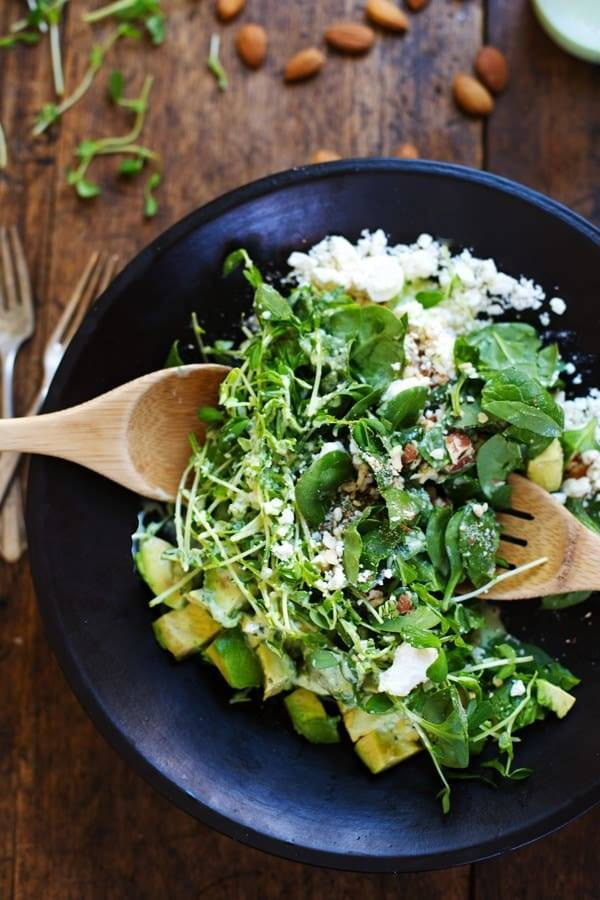 Green Goddess Detox Salad with wooden spoons.