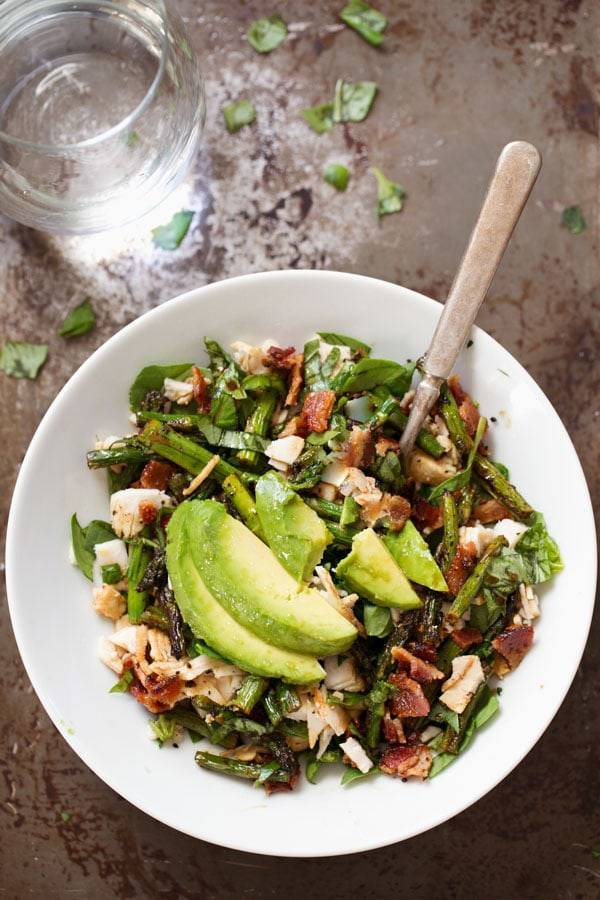 Chicken Bacon Avocado Salad with Roasted Asparagus in a white bowl.