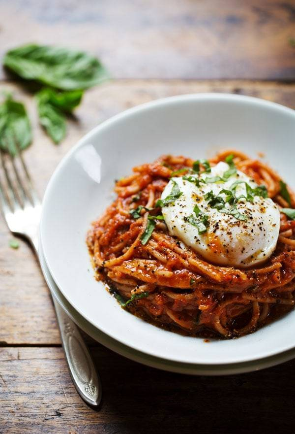 Spaghetti Marinara with Poached Eggs on a white plate with a fork.