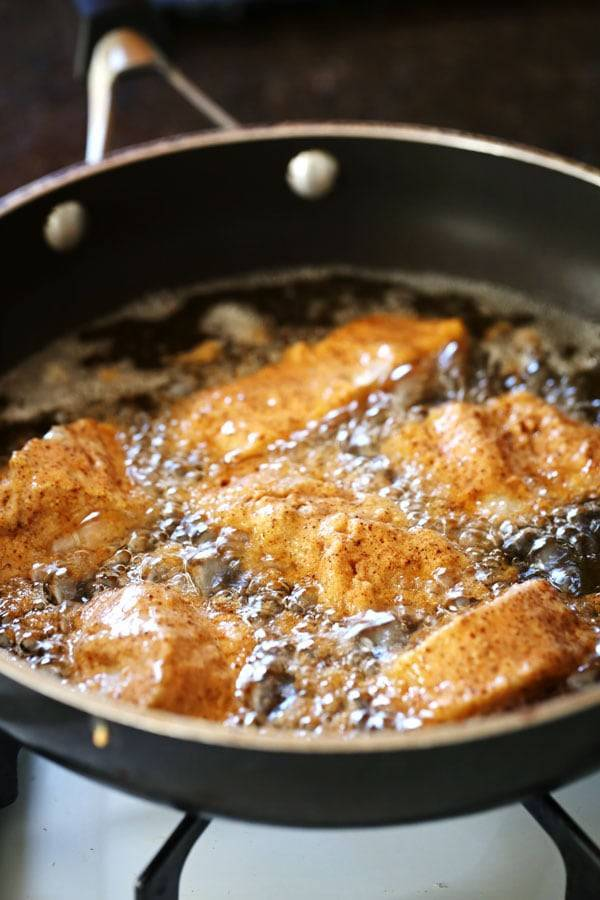 Fish frying in a skillet.