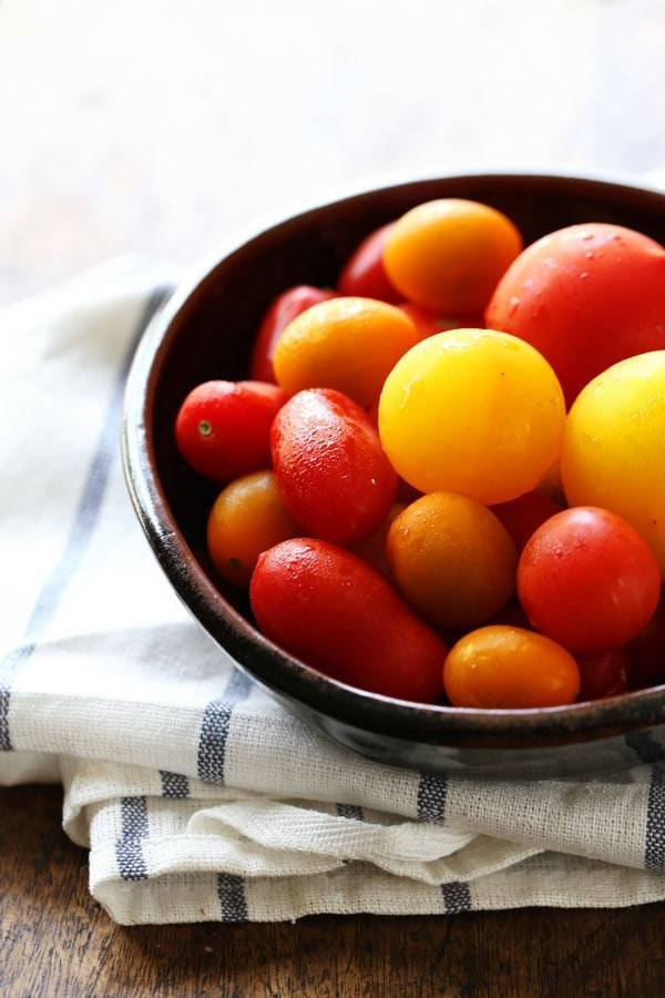 Tomatoes in a black bowl.
