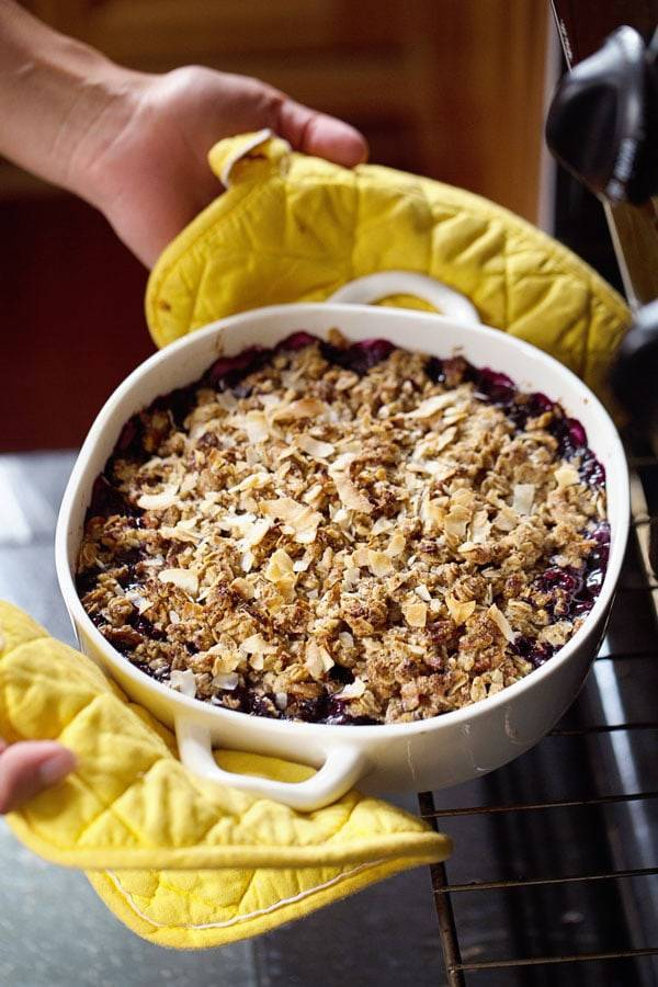 Simple Oat and Blueberry Crisp with yellow pot holders.