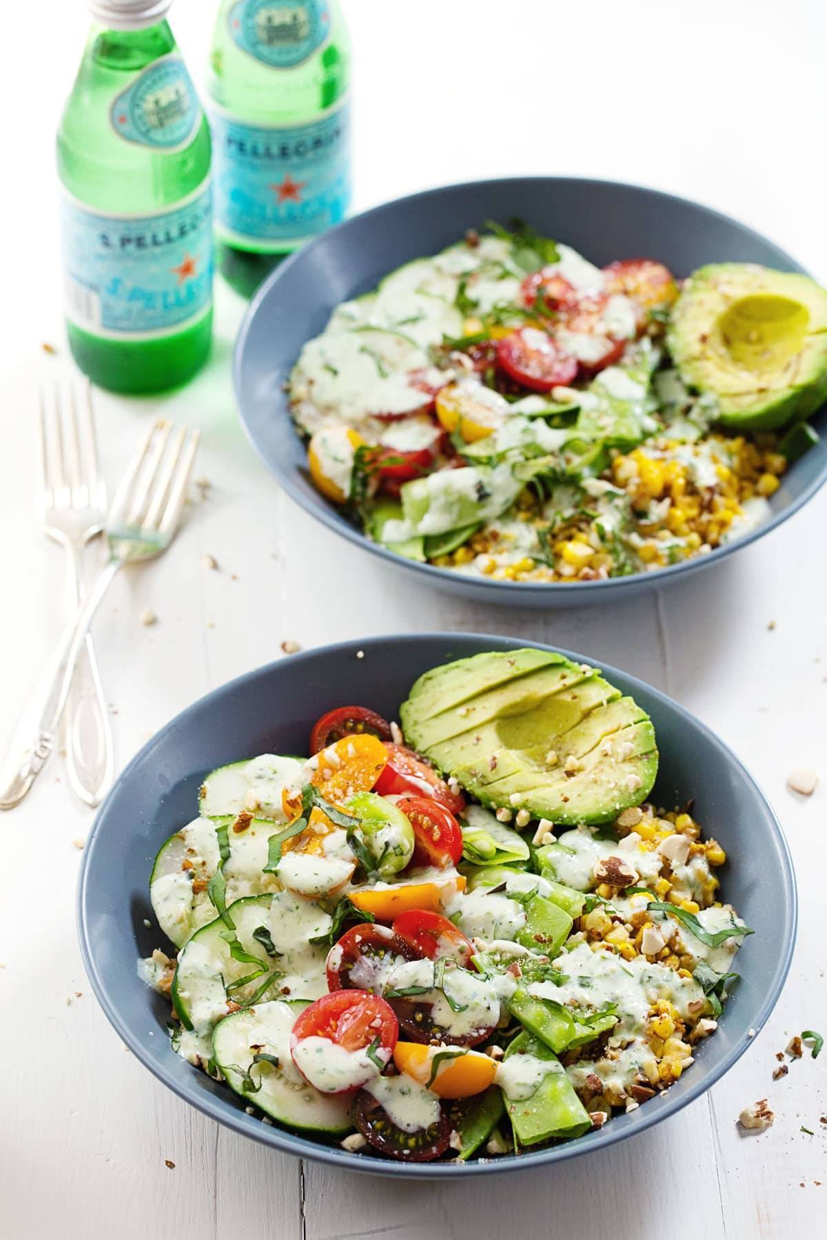 Rainbow Veggie Bowls with Jalapeño Ranch in blue bowls with sparkling water and forks.