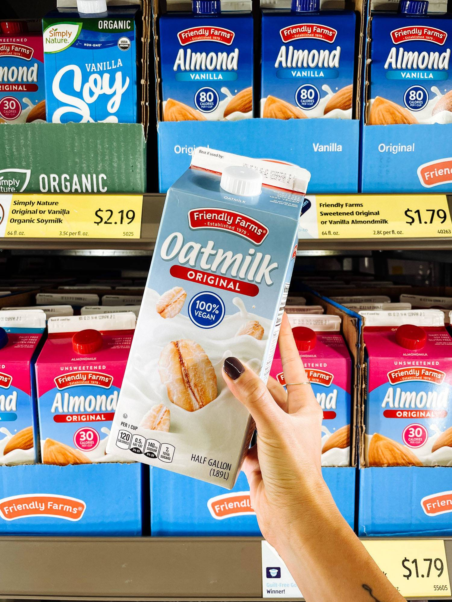 White hand holding oatmilk from ALDI.