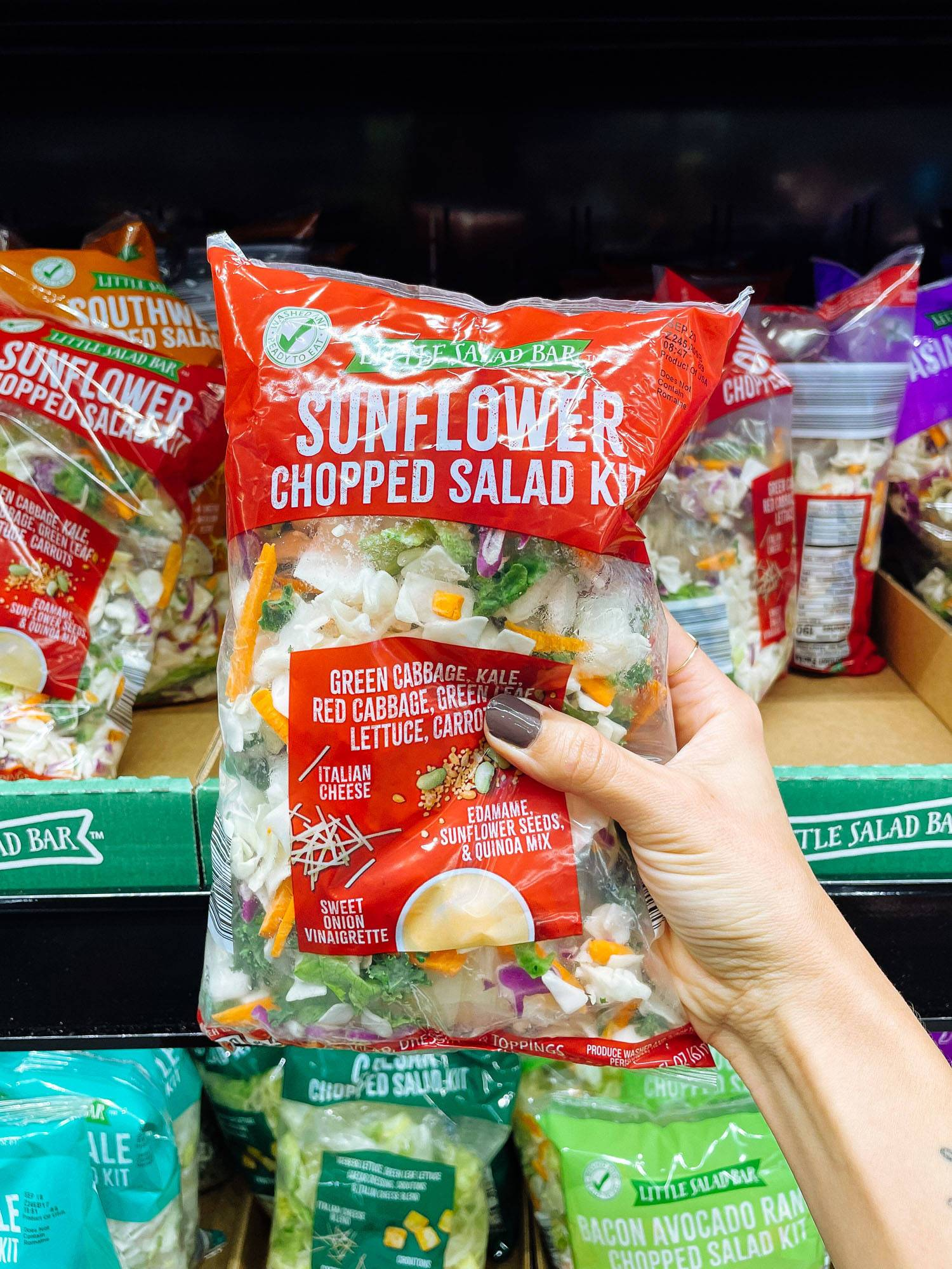 White hand holding a sunflower chopped salad kit from ALDI.