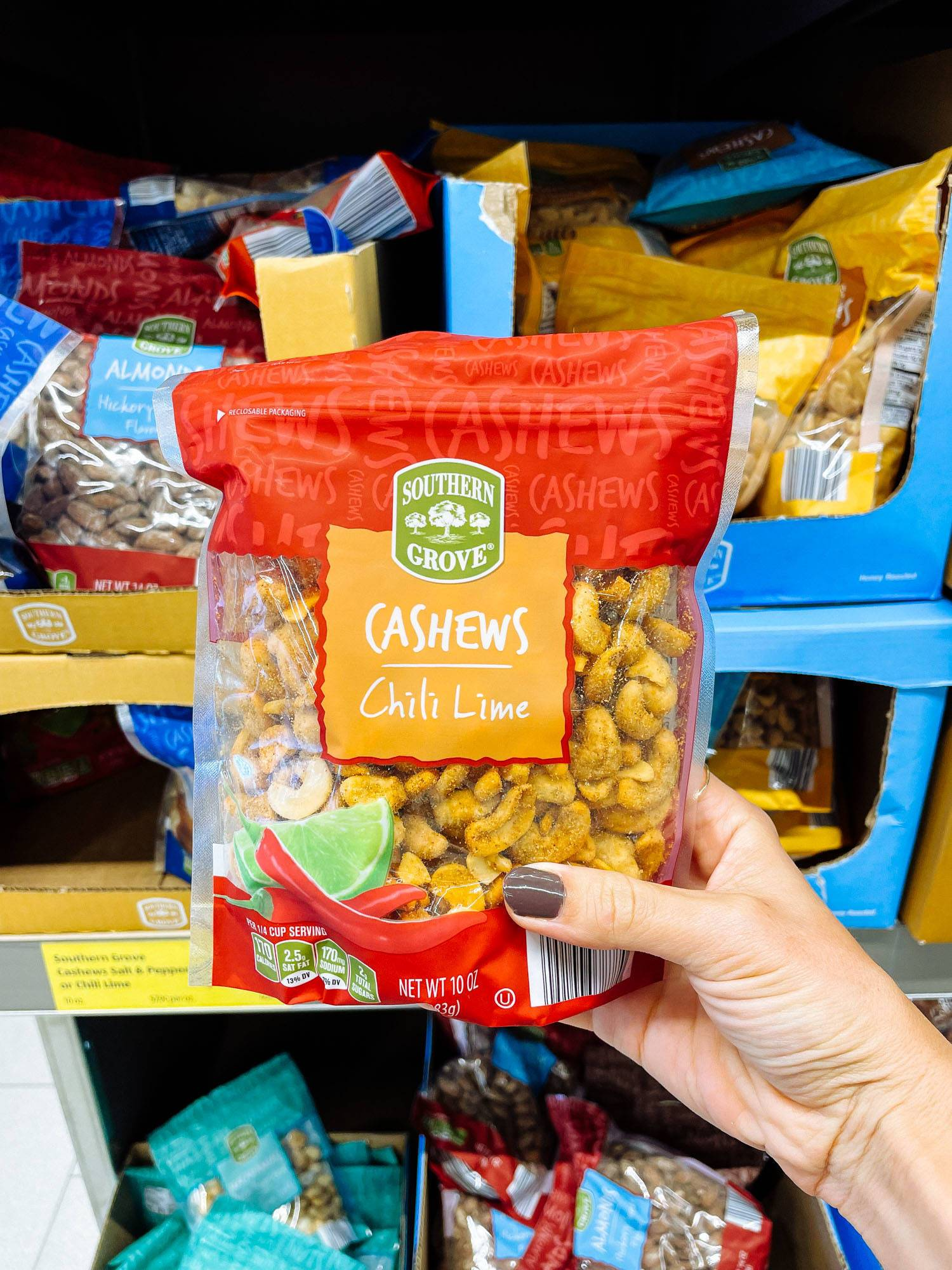 White hand holding chili lime cashews from ALDI.