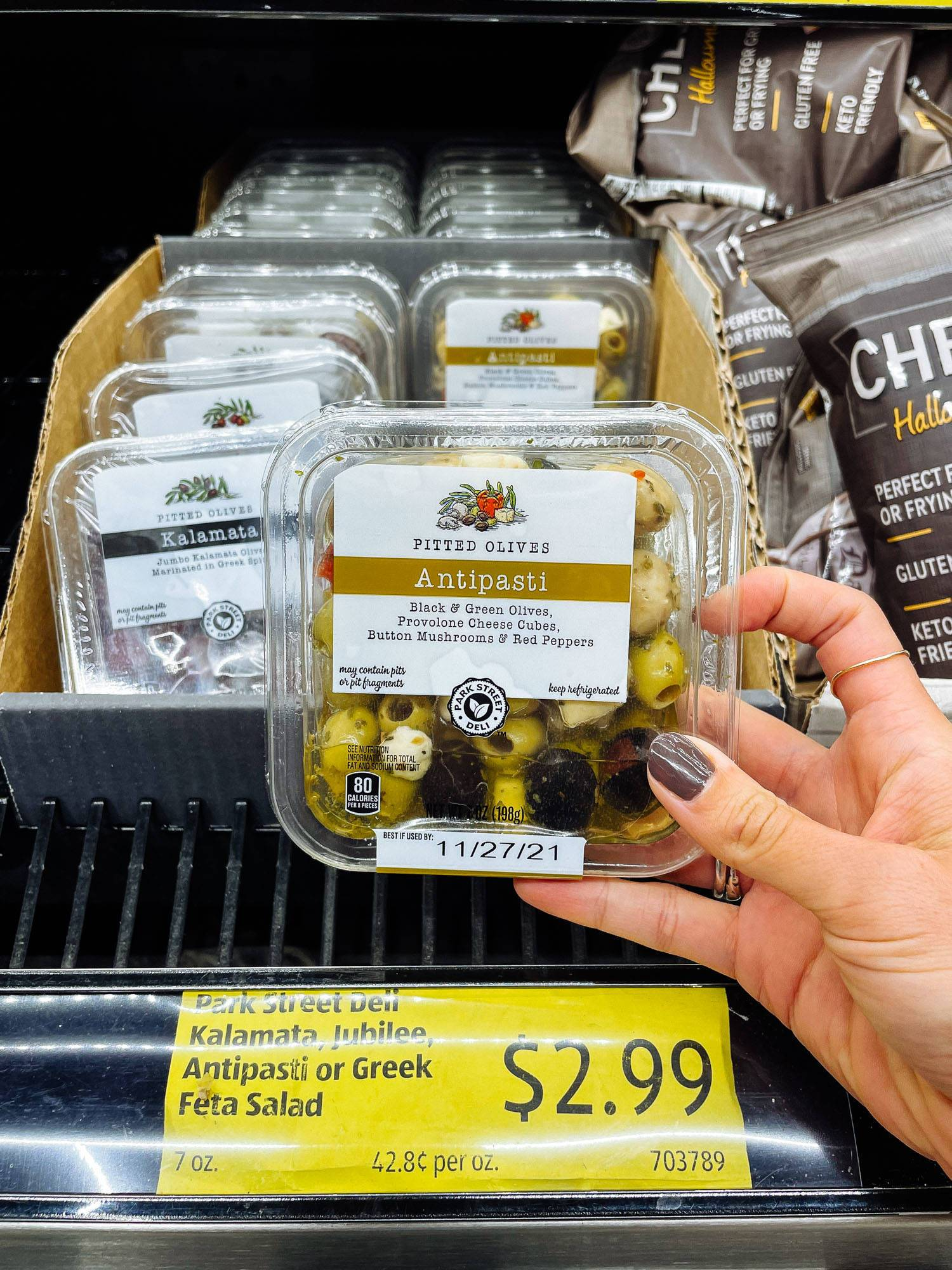 White hand holding antipasti olives and cheese container from ALDI.