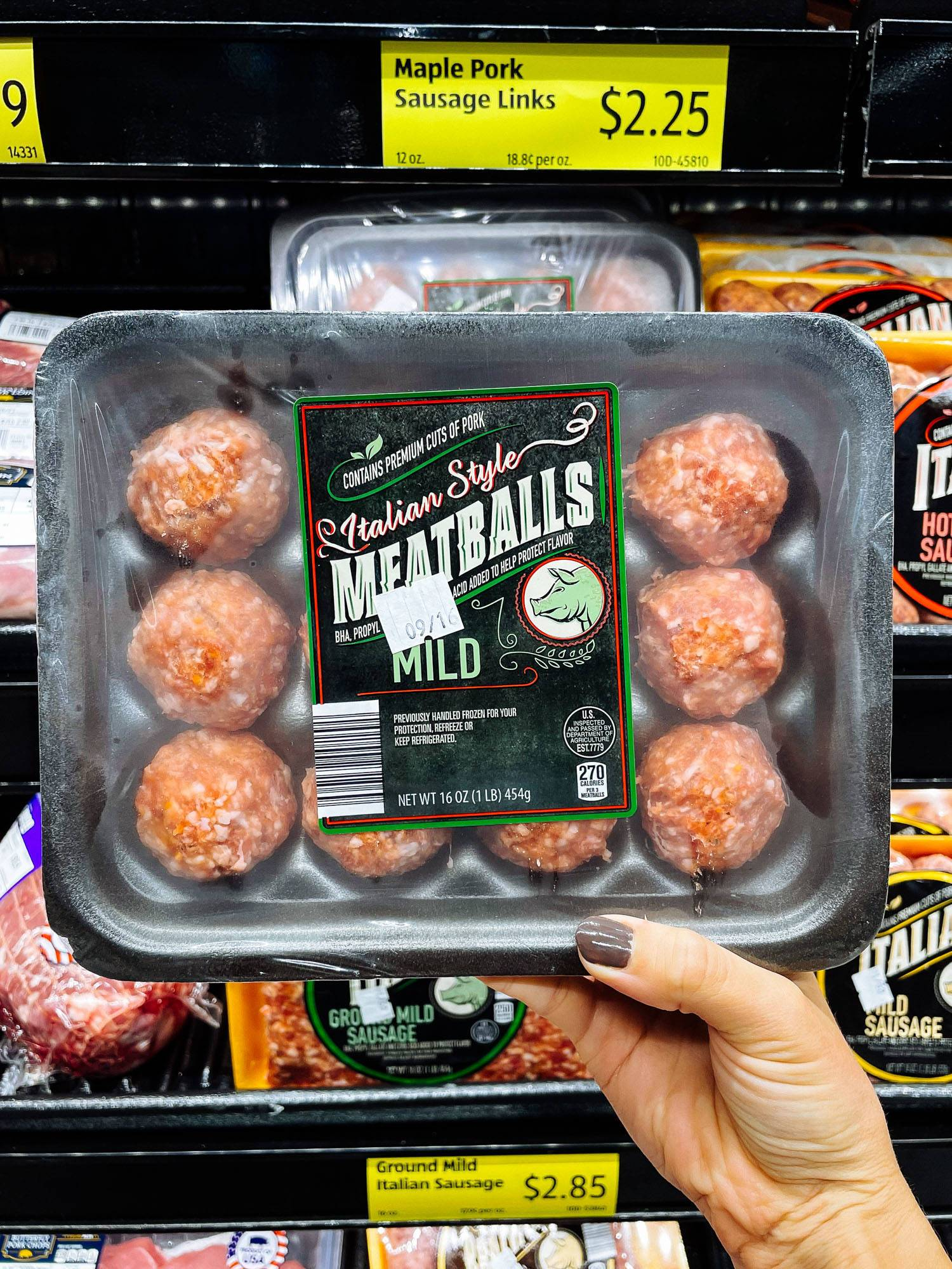 White hand holding Italian-style meatballs from ALDI.