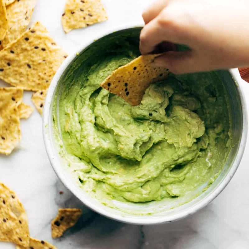 Avocado Dip in a bowl with chip.